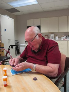 The old man learns to sort pills while in health care